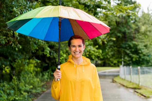 Mulher segurando um guarda-chuva colorido acima da cabeça