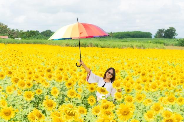 Mulher segurando um guarda-chuva em um campo de girassol.