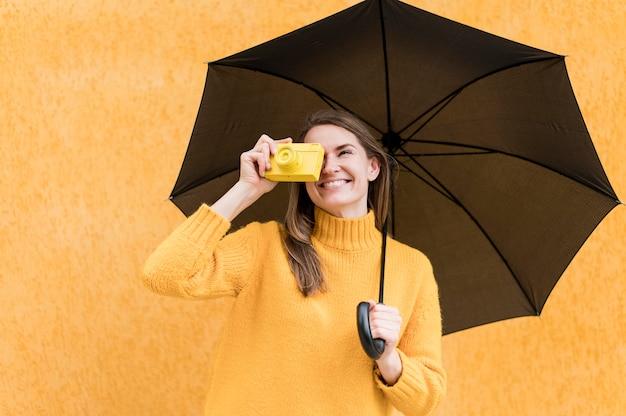 Mulher segurando um guarda-chuva preto e uma câmera amarela