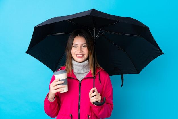 Mulher segurando um guarda-chuva sobre parede azul isolada