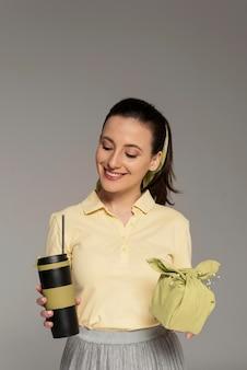 Mulher segurando um guardanapo e garrafa térmica reutilizáveis