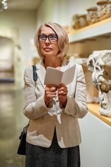 Mulher segurando um guia dentro de um museu