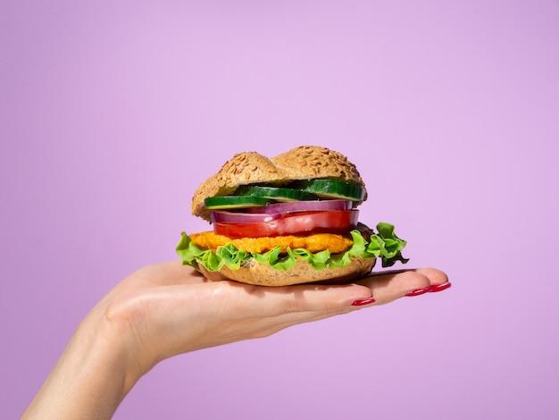 Mulher segurando um hambúrguer saboroso na palma da mão