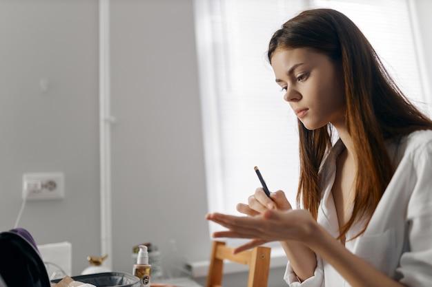 Mulher segurando um lápis e sentada à mesa com delineador de cosméticos