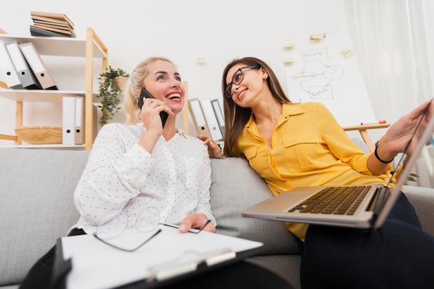 Mulher segurando um laptop e olhando para seu colega