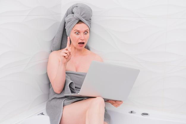 Mulher segurando um laptop na banheira e olhando espantado