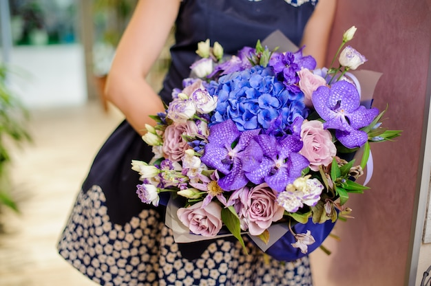Mulher segurando um lindo buquê roxo e azul de flores