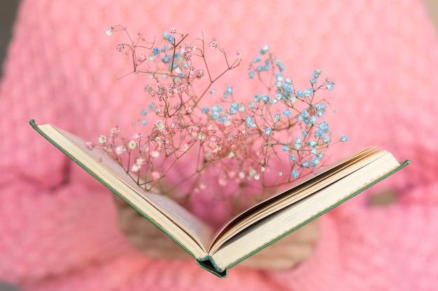 Mulher segurando um livro aberto com um buquê de flores secas dentro