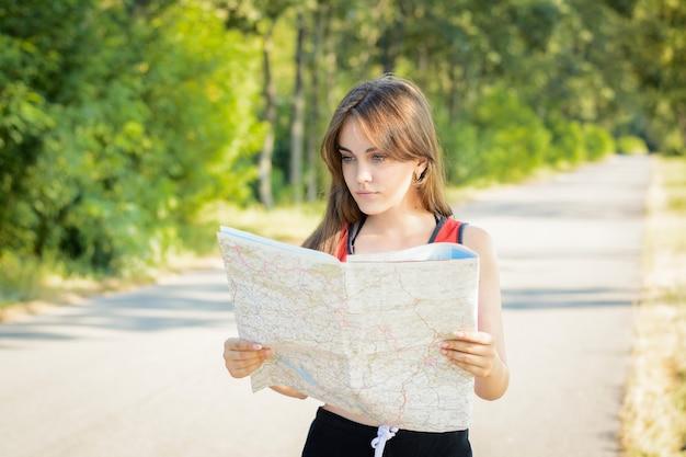 Mulher segurando um mapa e tentando encontrar um caminho