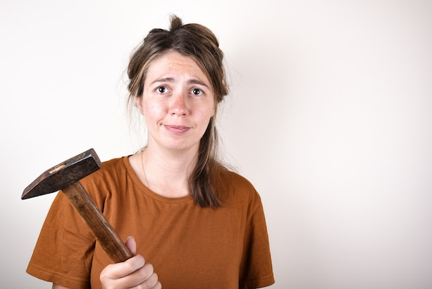 Mulher segurando um martelo para reforma de casa