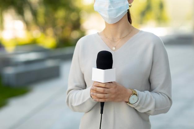 Mulher segurando um microfone enquanto usa uma máscara médica