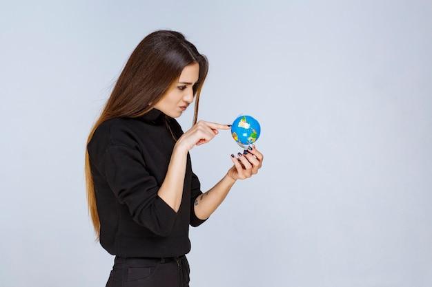 Mulher segurando um mini globo e encontrando locais nele.