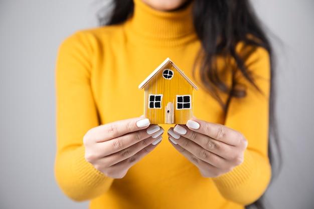 Mulher segurando um modelo de casa de madeira amarela