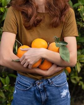 Mulher segurando um monte de laranjas