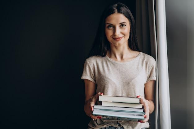 Mulher segurando um monte de livros