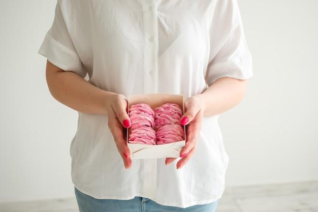 Mulher segurando um pacote com fundo branco de marshmallows caseiros rosa