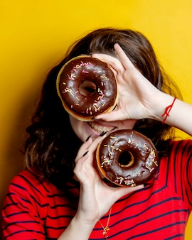 Mulher segurando um par de donuts com chocolate