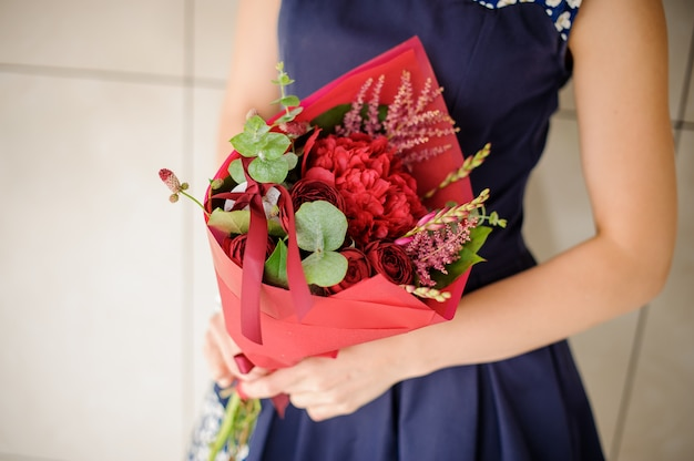 Mulher segurando um pequeno buquê de flores