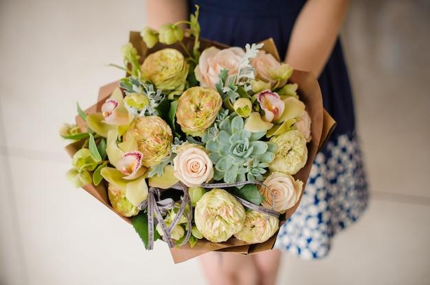Mulher segurando um pequeno buquê verde de flores nas mãos