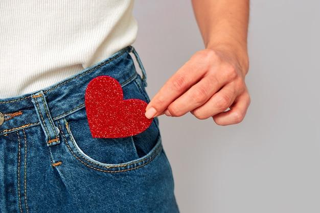 Mulher segurando um pequeno coração vermelho cintilante, colocando-o ou tirando o bolso da calça jeans. compartilhando e recebendo cartões de dia dos namorados, mantendo o amor com você