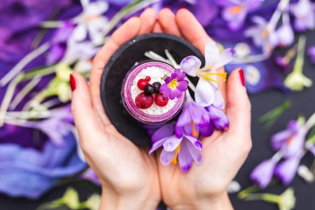 Mulher segurando um pote de smoothie vegan coberto com frutas vermelhas e cercado de flores