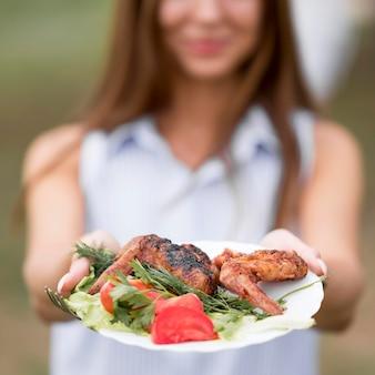 Mulher segurando um prato com churrasqueira ao ar livre
