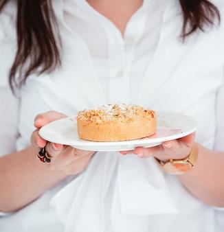 Mulher segurando um prato com torta de maçã