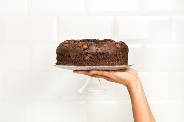 Mulher segurando um prato de bolo com um bolo de chocolate em frente à parede com ladrilhos do metrô