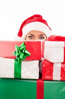 Mulher segurando um presente de natal na frente do rosto