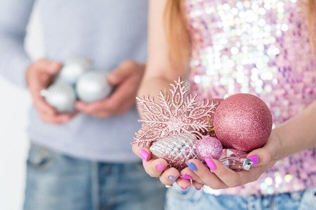Mulher segurando um punhado de bolas brilhantes de ouro rosa e um floco de neve
