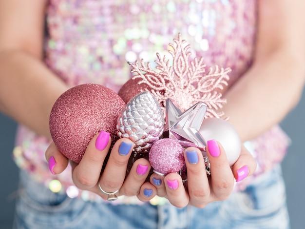 Mulher segurando um punhado de brinquedos sazonais tradicionais. ouro rosa enfeites brilhantes floco de neve pinho e estrela.