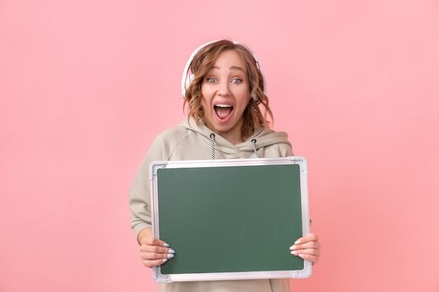 Mulher segurando um quadro-negro vazio sobre um fundo rosa feliz mulher caucasiana de 30 anos de idade vestida com fones de ouvido com capuz grande segurar placa verde em branco fotos de estúdio publicidade promover apresentação
