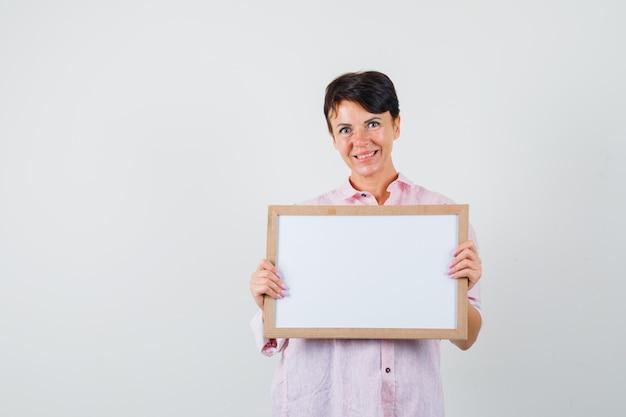 Mulher segurando um quadro vazio na camisa rosa e olhando alegre, vista frontal.
