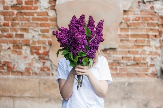 Mulher segurando um ramo vívido de flores lilás contra a parede de tijolos