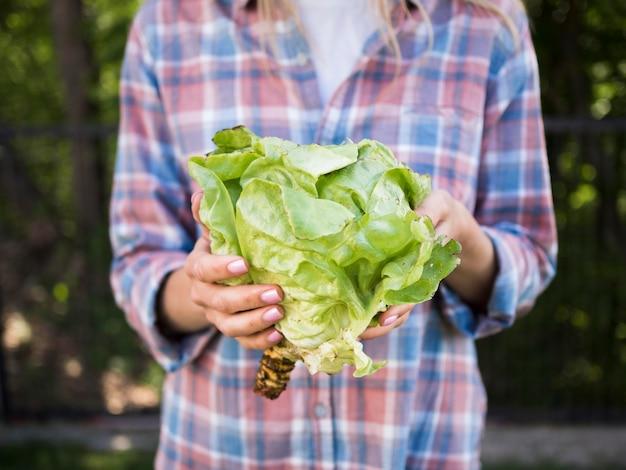 Mulher segurando um repolho verde