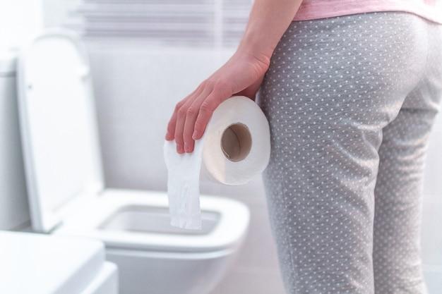 Mulher segurando um rolo de papel e sofrendo de diarréia, constipação e cistite no banheiro. dor de estômago durante a tpm. cuidados de saúde