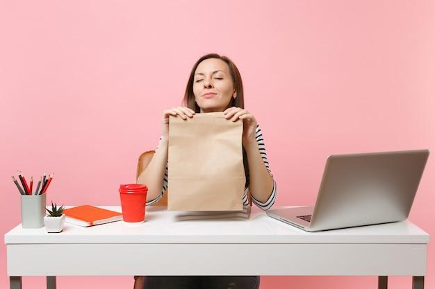 Mulher segurando um saco de papel artesanal em branco vazio, cheirando o cheiro de trabalho no escritório com o laptop do pc