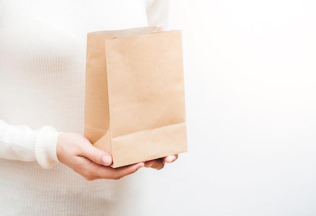 Mulher segurando um saco de papel de perto