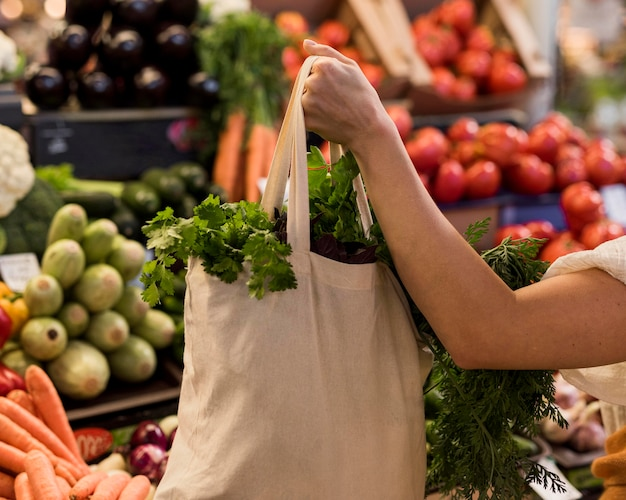 Mulher segurando um saco de vegetais