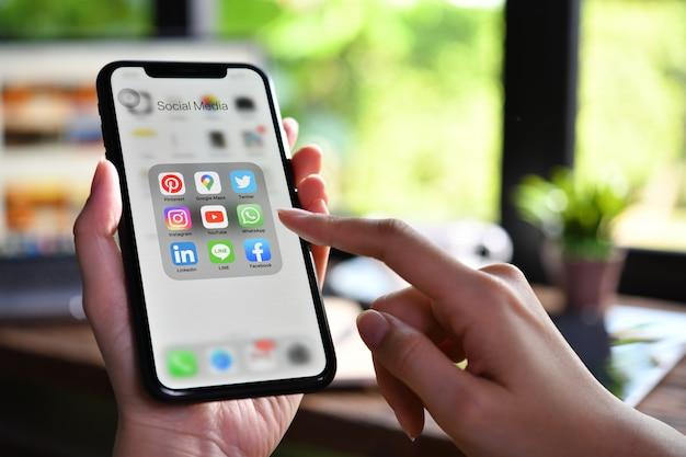 Mulher segurando um smartphone com ícones de mídias sociais na tela no café.