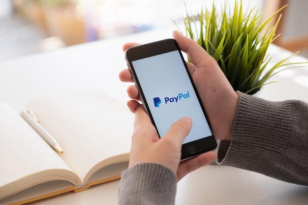 Mulher segurando um smartphone com pagamentos on-line de serviço na tela.