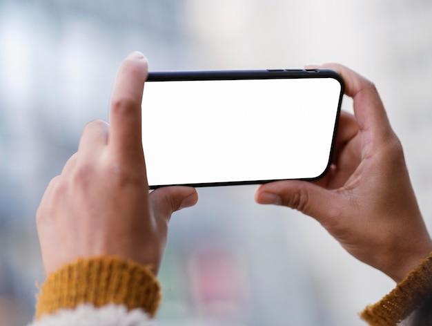 Mulher segurando um smartphone com tela vazia