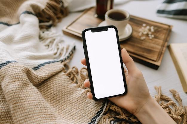 Mulher segurando um smartphone com uma tela branca simulada, sentada na cama em casa e bebendo café.