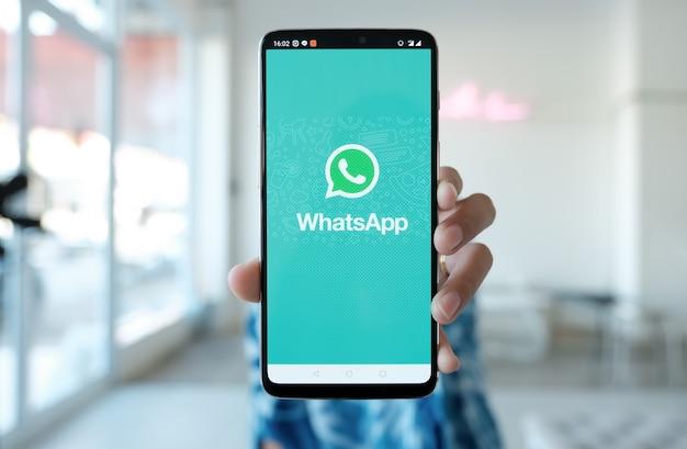 Mulher segurando um smartphone e appstore aberto pesquisando serviço de internet social whatsapp na tela.