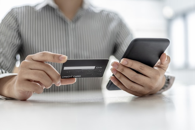 Mulher segurando um smartphone e um cartão de crédito, ela preenche os dados do cartão de crédito para pagar as compras feitas pelo aplicativo do smartphone. conceito de compra online e pagamento com cartão de crédito.