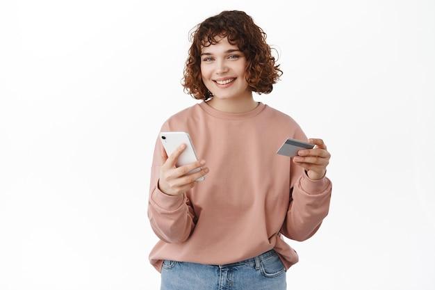 Mulher segurando um smartphone e um cartão de crédito, pagando no aplicativo, usando o aplicativo da loja, pedindo algo, parado no branco