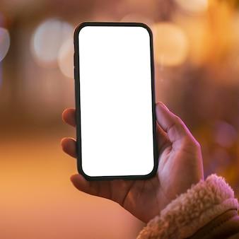 Mulher segurando um smartphone em branco com efeito bokeh ao redor