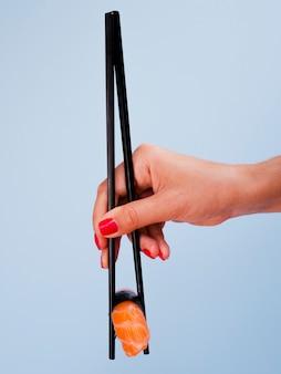 Mulher segurando um sushi de salmão sobre um fundo azul
