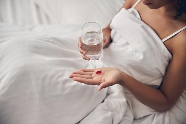 Mulher segurando um tablet e um copo d'água