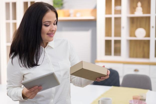 Mulher segurando um tablet e uma caixa